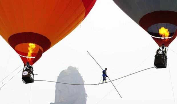 Am Rande: Akrobat zwischen zwei Luftballons