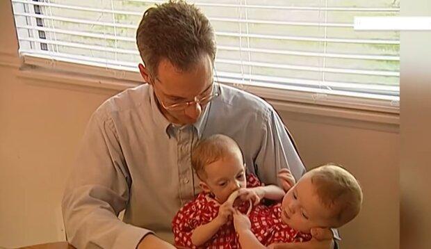 Vater mit siamesischen Zwillingen. Quelle: YouTube Screenshot